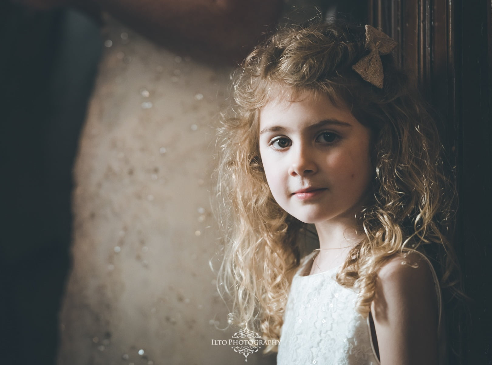 Pretty flower girl stands in natural light and shade.