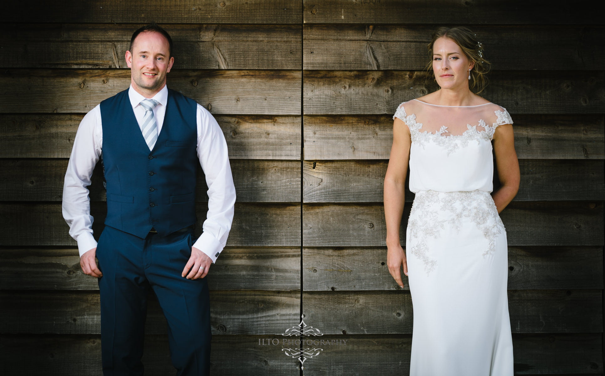 Bride and groom lean against a barn at Dodford Manor Northampton