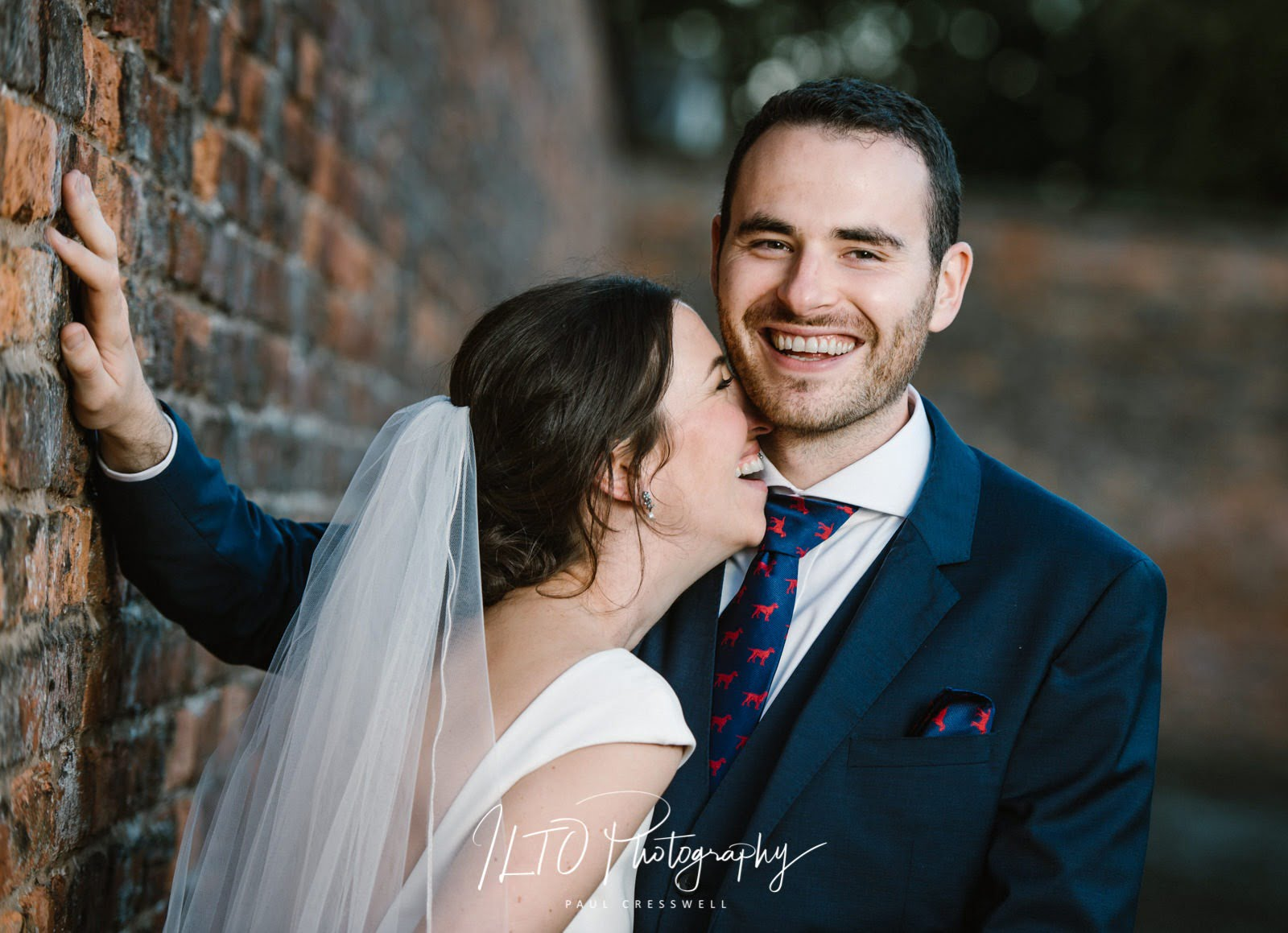 Bride leans in to the groom laughing as they lean against brick wall.
