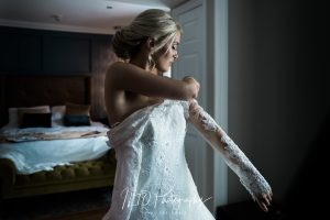 Stunning bride slips an arm in to her wedding dress. Natural light. Yorkshire Wedding Photographer.