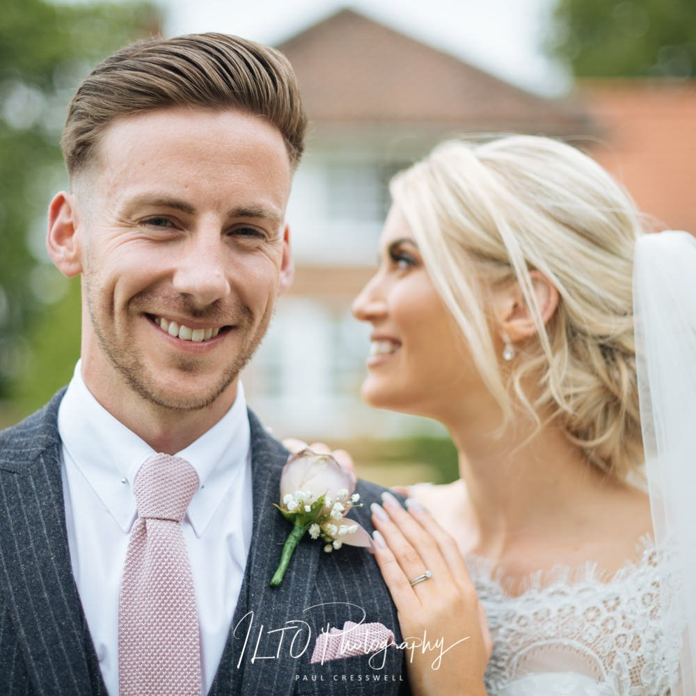 Handsome groom stands with his beautiful bride just behind him. The bride is looking to the side and the groom is looking the camera. ILTO Photography