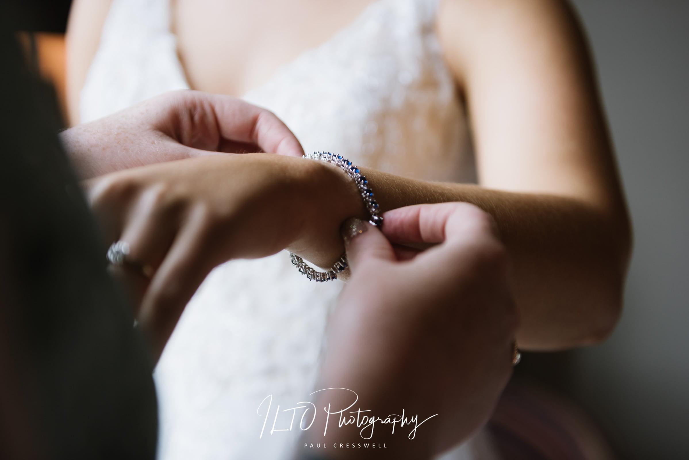 Leeds bride putting on jewellery wedding photo