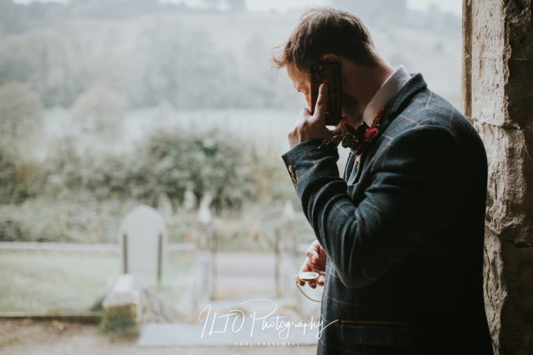 Groom on a phone at a wedding checking his watch