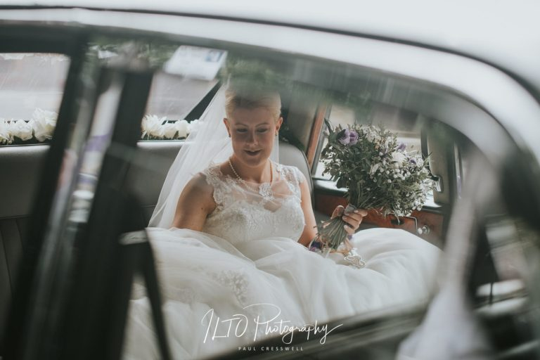 Reportage classic wedding photographer west yorkshire bride in wedding car with flowers