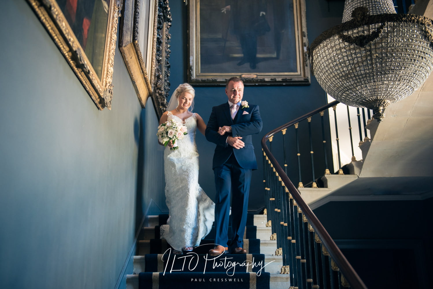 Bride and father walk down elegant stairs stubton hall